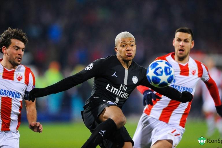 Kylian Mbappé entre deux joueurs de l'Étoile Rouge de Belgrade.